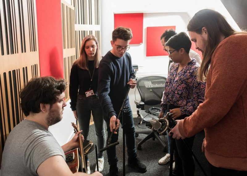 Abbey Road Institute teaching space incorporates GIK Acoustics Alpha Series and 242 Acoustic Panels in studio where students are adjusting microphone placement around guitarist