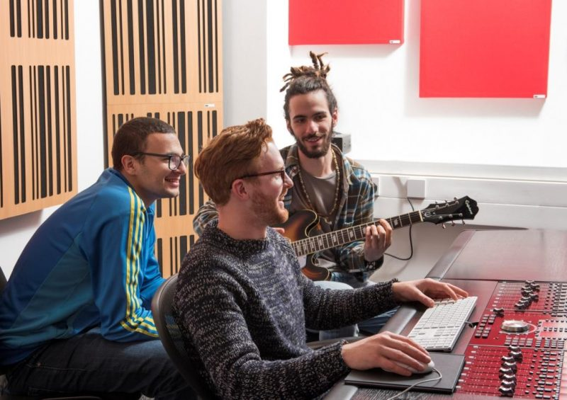 Musicians and producers learning in Abbey Road Institute Mixing Room with GIK Acoustics blonde 1D Alpha Corner Traps and red 242 Acoustic Panels squares behind the listening position